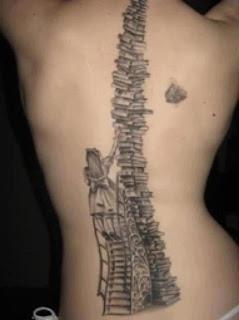 Woman's back with a tattoo of a little girl climbing a ladder to reach a book from a tall stack.