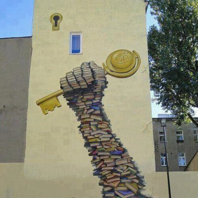 Painting on a tower wall of an arm made of books holding aloft a giant key.
