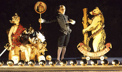 Puppet Shakespeare surrounded by skull, bear, doll dressed as Scottish king and other props.