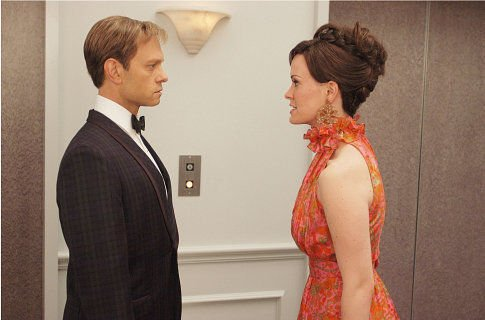 White man in dinner suit and white brunette woman in orange dress face to face.