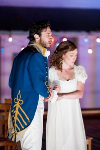 Man in blue army tailcoat and woman in white muslin dress clasp hands.