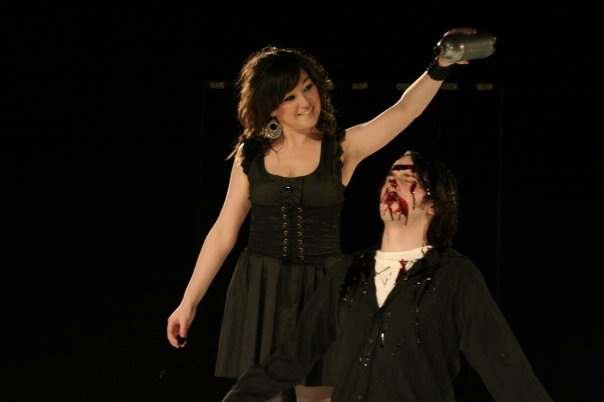 Young woman pours stage blood from a bottle over a kneeling man.