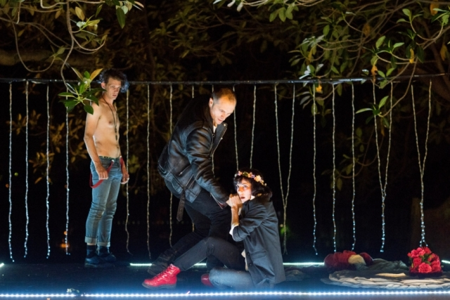 Nighttime, woman with flowers in her hair and two men, one shirtless, one leather jacket.