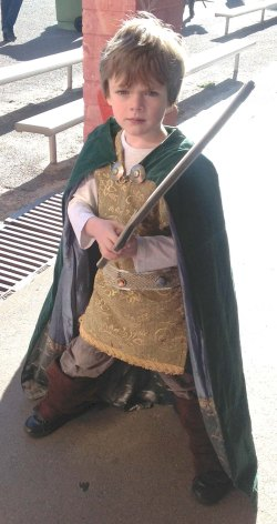 Five year old boy in cloak holding sword.