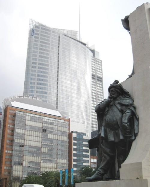 Statue of Falstaff leaning on a stone plinth, skyscrapers in background.