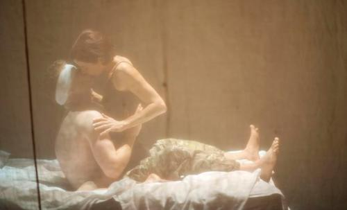 Woman kissing injured man on army camp bed, seen through a scrim.