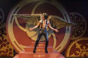 Young man in leather pants, no shirt, mechanical wings.