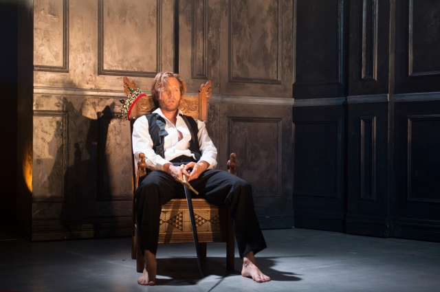 Middle aged, blonde man in evening dress, undone tie, bare feet, seated on a wooden throne holding a sword.