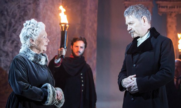 Judi Dench and Kenneth Branagh in Victorian winter coats, illuminated by a guard holding a flaming torch.
