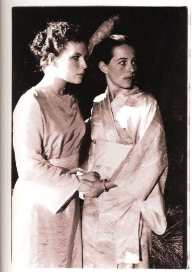 Two young white women in long gowns hold hands.